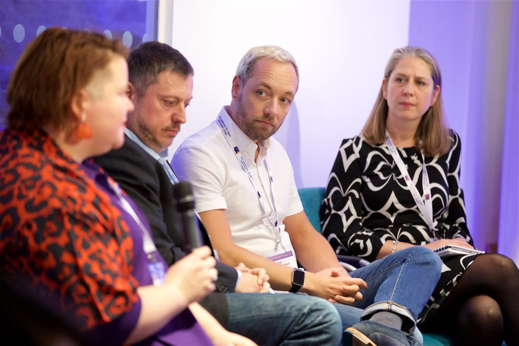 4 people sitting talking at a panel